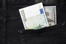 One hundred euro and one hundred dollar bills sticking out of the pocket of black jeans