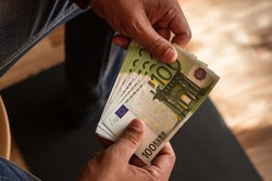 one hundred euro banknotes in working hard palms of man against black and brown background