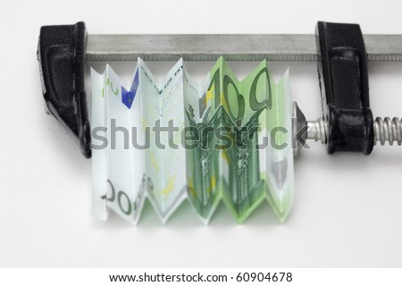 One hundred euro bill squeezed in a clamp on white background
