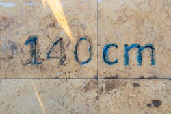 one hundred forty cm number is written on a stone slab
