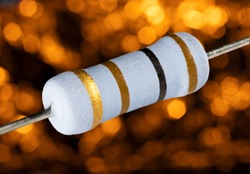 One hundred ohm rated resistor on a blurred orange background