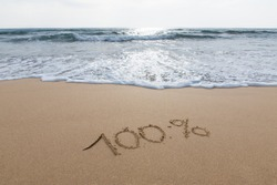 One hundred percent written on the wet sand by the sea