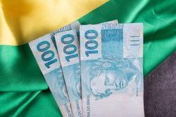 One hundred reais notes on Brazilian flag.