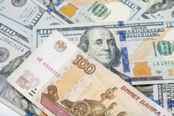 One hundred rubles lying on american dollars as a symbol of weakness russian national currency and strengthening of american dollar.