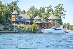 One Island with the white house with a white boat  in Thousand Islands Region in summer in Kingston, Ontario, Canada