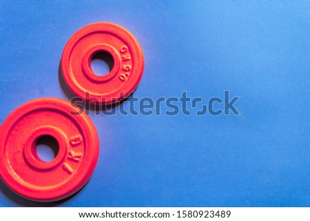 one kilogram and half kilogram red gym weight on blue background