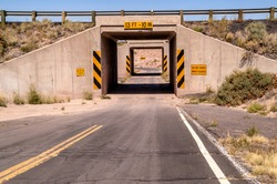 One lane tunnel under a highway bridge with a sharp curve at the end blocking the view of oncoming traffic.  There are plenty of warning and caution signs.