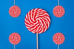 One large round Christmas Lollipop and four small ones lie on a blue background. Sweet round candy of red and white color. Five sucking lollipops in the shape of a spiral of different size