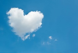One large white cloud in the shape of a heart in the blue sky