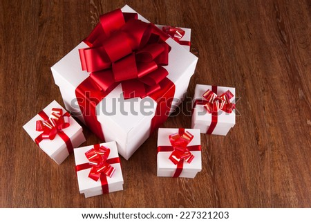 one large white gift box and white gift boxes on a wood background
