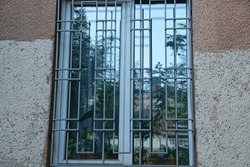 one large white window behind a gray iron grating on a brown concrete wall of a house outside