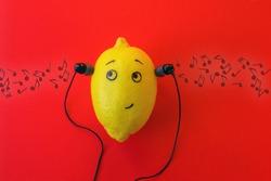 One lemon in the phone's headphones is enjoying music. Musical concept.