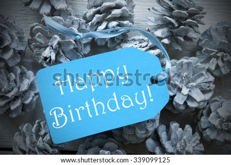 One Light Blue Label On Fir Cones And White Wooden Background. English Text Happy Birthday Vintage Or Retro Style Used As Winter Or Christmas Background With Frame
