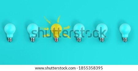 Photo of  One light bulb on among many off. cyan background. Concept of creativity and idea