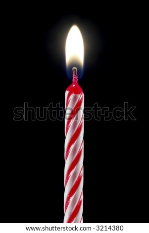 One lit birthday candle isolated over black.