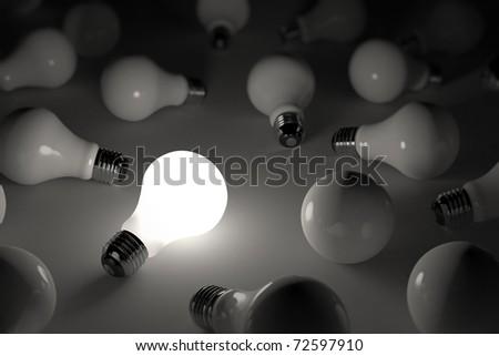 One lit light bulb amongst other broken light bulbs - shallow depth of field
