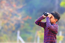 One little boy use binoculars watching bird in nature with blurry background.