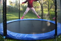 One little European girl jumps on a outdoor 8ft trampoline with outside safety soft net fence on green grass in the suburban Garden at Sunny summer day, active sport recreation