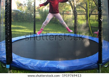 One little European girl jumps on a outdoor 8ft trampoline with outside safety soft net fence on green grass in the suburban Garden at Sunny summer day, active sport recreation Stock fotó ©