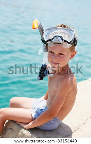 one little smiling boy sitting on pier near red sea with snorkeling gear on