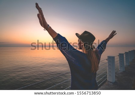 One lonely free carefree enjoy traveler woman in hat with open outstretched arms standing on sea pier at sunset. Happy freedom concept and enjoying life #1556713850