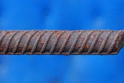 one long brown iron rod from rebar in rust on a blue background