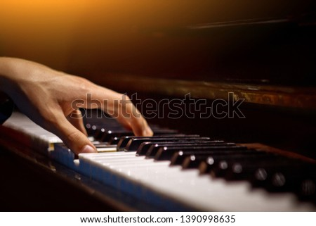 one male hand on the piano. The palm lies on the keys and plays the keyboard instrument in the music school. student learns to play. hands pianist. black dark background. #1390998635