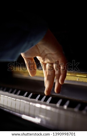 one male hand on the piano. The palm lies on the keys and plays the keyboard instrument in the music school. student learns to play. hands pianist. black dark background. vertical. #1390998701