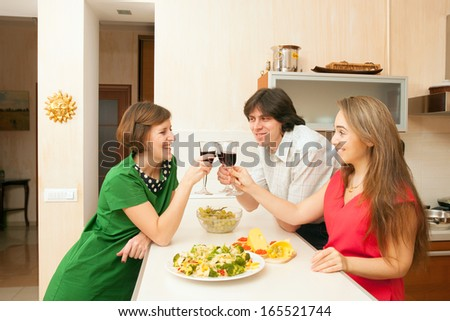 One man and two woman drink red wine on kitchen