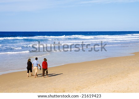 One man and two women taking a peaceful walk on the beach
