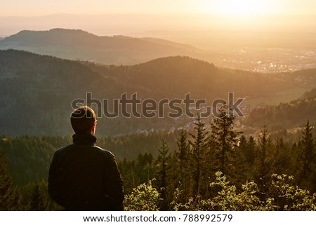 One man looking a sunrise on a peak of a mountain. Back of the man looking a forest. Handsome male in the nature. Sunrise from the top of a mountain with a town and a man.