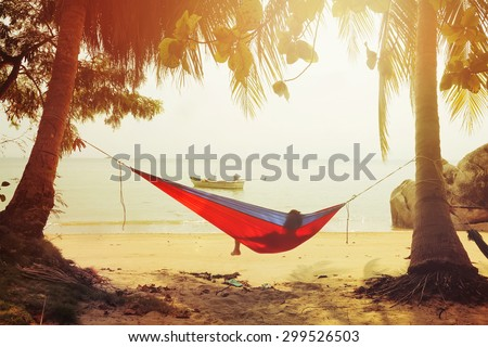 One man looking on the sea in hammock on a sand beach at sunset.Vintage effect added for create atmosphere