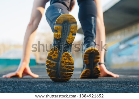 one man on the start line awaits the start of the sprint. stadium, rubber track. athletics competitions. Track and field runner in sport uniform at starting position. athlete, back view, close up.