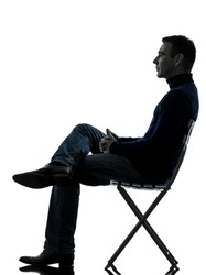 one  man sitting looking up full length in silhouette studio isolated on white background