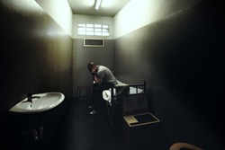 One man sitting on a bed in a small room of a dark prison.