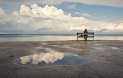 One man sitting on a bench on the beach with beautiful clouds in the background