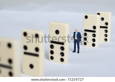 one man standing on pile of domino cubes - stock photo