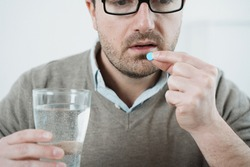 One man taking medicine pills isolated on background
