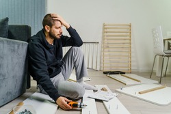 One Man with beard alone Putting Together Self Assembly Furniture at Home holding electric screwdriver looking the instructions frustrated desperate hold head - DIY concept real people copy space