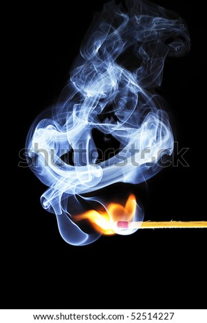 one match is igniting in front of black background with blue smoke