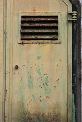 One metal door with rusty slots and the zipper