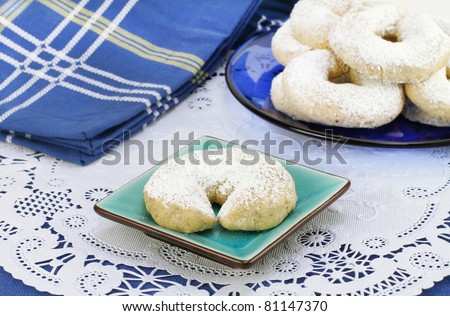 One Mexican Wedding Cookie on a colorful small plate.  Set on doily with more cookies in the background.