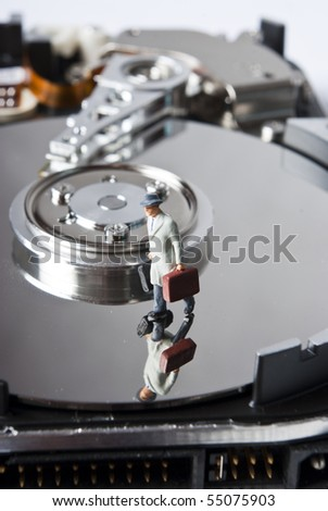 one miniature man with suitcase on hard drive