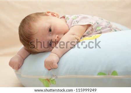 One month old baby lying on his tummy on the blue pillow. Baby looking at the camera. Selective focus on baby face