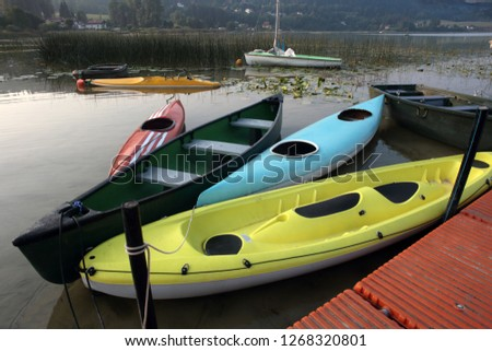 one morning at the start of a lake, on the surface of the fleet a colorful set of canoes, wooden boat and small sailboat leisure nautical.