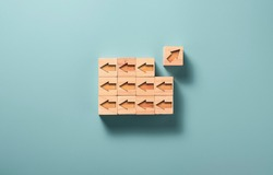 One of arrow move to opposite direction with others arrow which carved on wooden block cubes for  business disruption and different thinking idea.