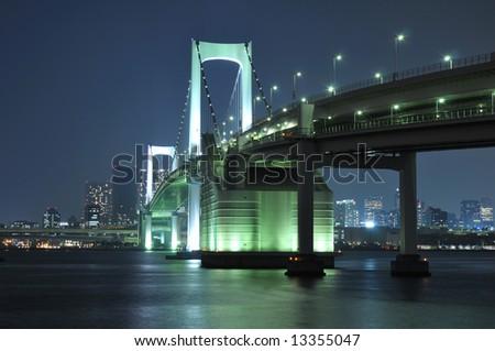 one of famous Tokyo landmarks, Tokyo Rainbow bridge over bay waters with scenic night illumination