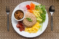 One of favorite main courses the thai food, Stir fried shrimp paste rice with caramelized pork, chinese sausage, omelette, vegetables, Eat hot food, Use serving Spoon, always wash hand in covid19 cris