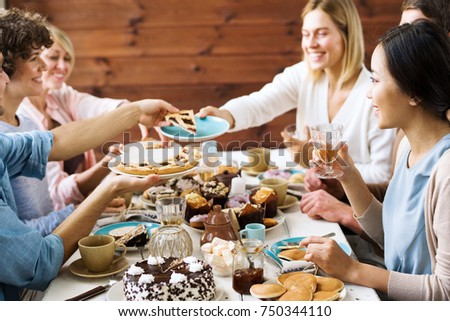 One of guests asking for slice of sweet pie during home celebration of holiday by festive table