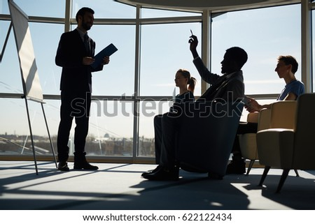 One of managers raising hand to answer question of business coach